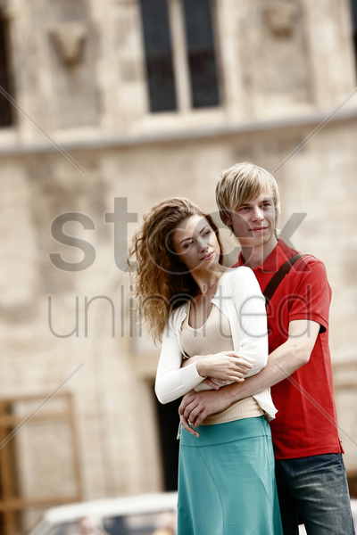 a guy hugging his girlfriend from the back stock photo