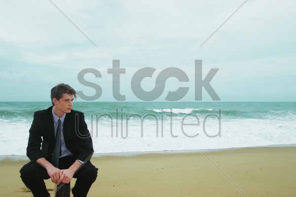 a guy in a business suit sitting on his briefcase on the beach stock photo