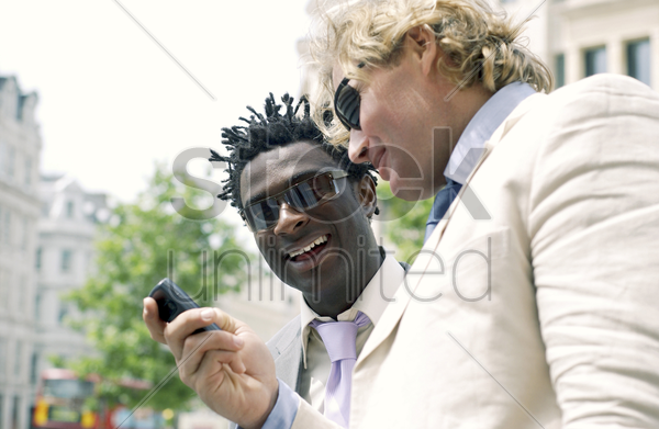 a guy in white suit and sunglasses showing his african american friend the messages in his hand phone stock photo