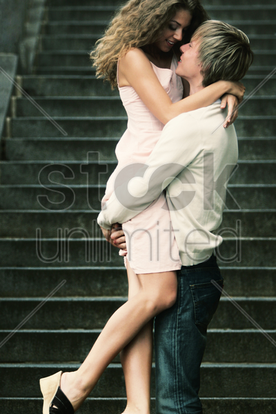 a guy lifting his girlfriend up stock photo