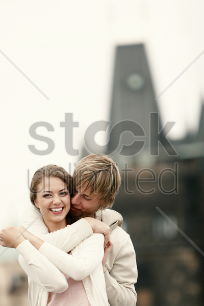 a guy locking his arm around his girlfriend's shoulder stock photo