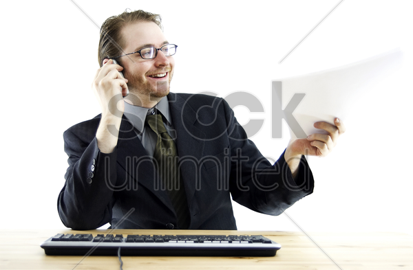 a guy passing a paper while talking on his hand phone stock photo