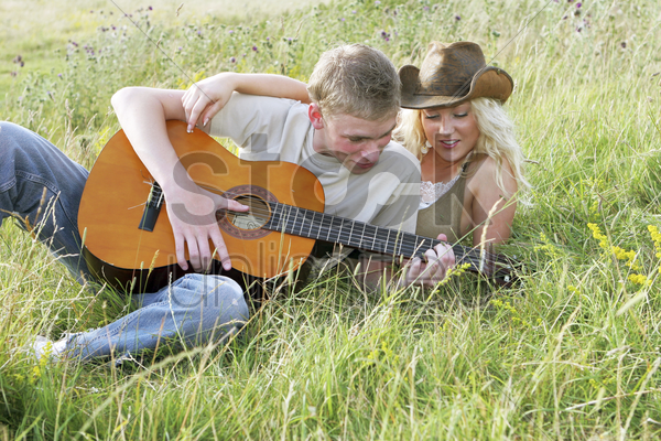 a guy playing a song on his guitar for his girlfriend stock photo
