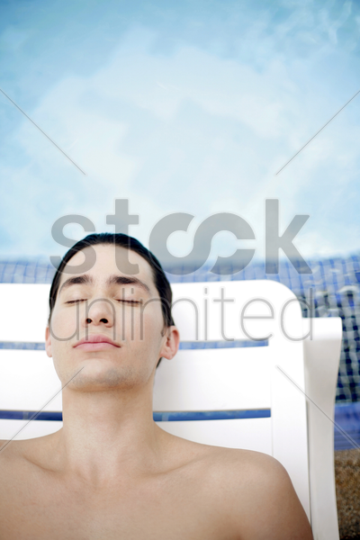 a guy relaxing by the poolside stock photo
