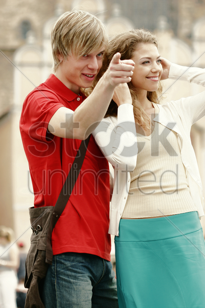 a guy showing something to his girlfriend stock photo