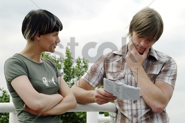 a guy trying to figure out the place wrote on the address book whiles his girlfriend watching stock photo