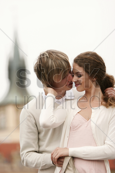 a guy trying to kiss his girlfriend stock photo