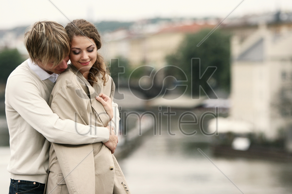 a guy warming up his girlfriend by hugging her from the back stock photo