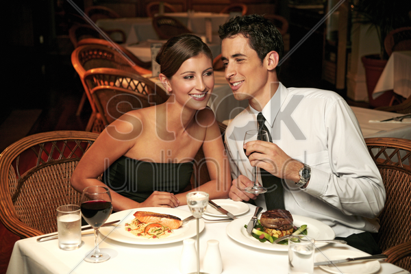 a guy whispering to his girlfriend stock photo