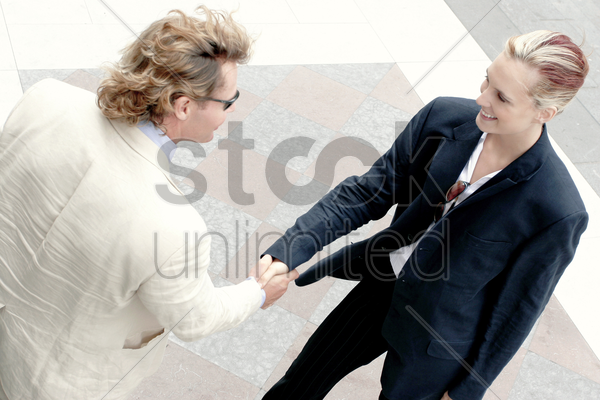 a handshake between a man and a woman stock photo