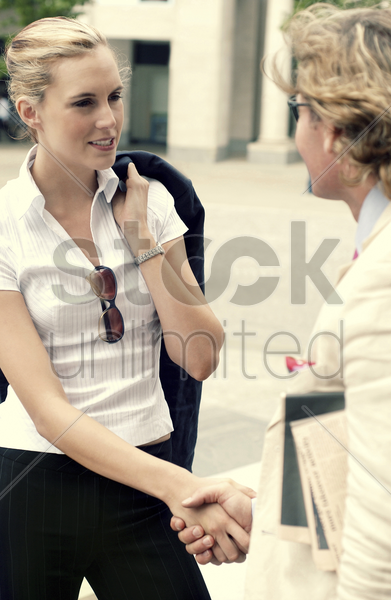 a handshake between a woman in black pants and a man in white suit stock photo