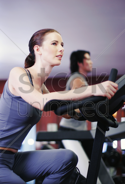 a lady and her boyfriend exercising in a gymnasium stock photo
