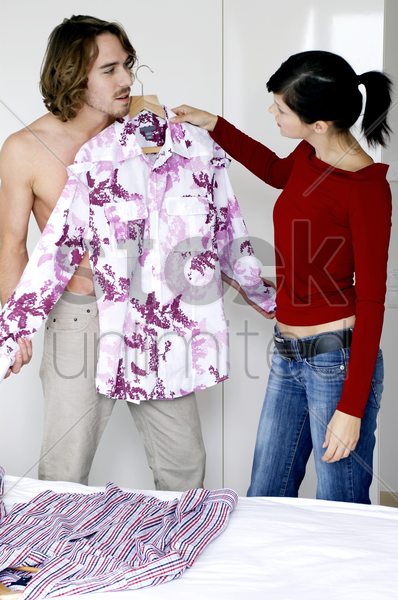 a lady helping her boyfriend to choose clothes stock photo