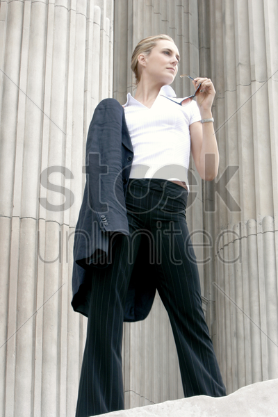a lady holding a sunglass with her coat hanging on her shoulder stock photo