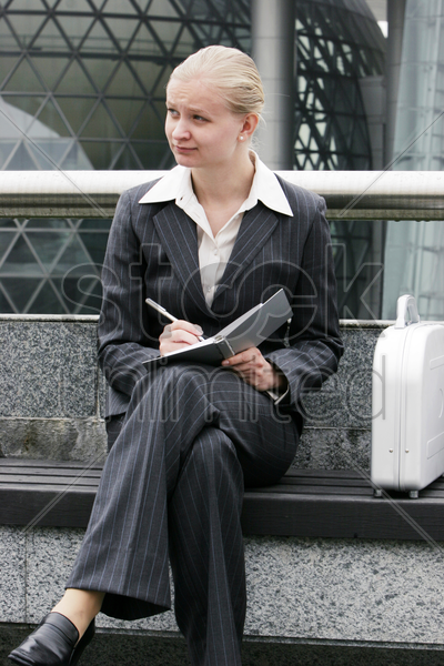 a lady in business suit sitting on the bench writing notes stock photo