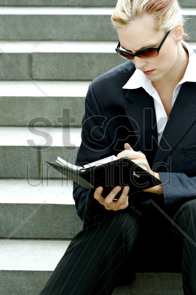 a lady in business suit with sunglasses sitting on the stairs writing her organizer stock photo