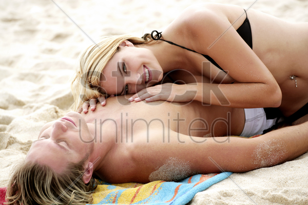 a lady listening to her boyfriend's heartbeat as he is sleeping stock photo