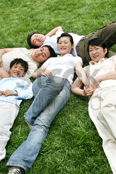a lady lying on the grass with her brothers and parents stock photo