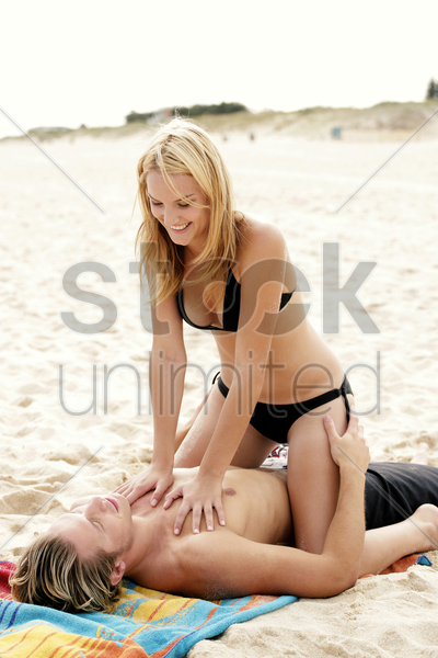 a lady pumping her boyfriend's heart as he is lying on the beach stock photo