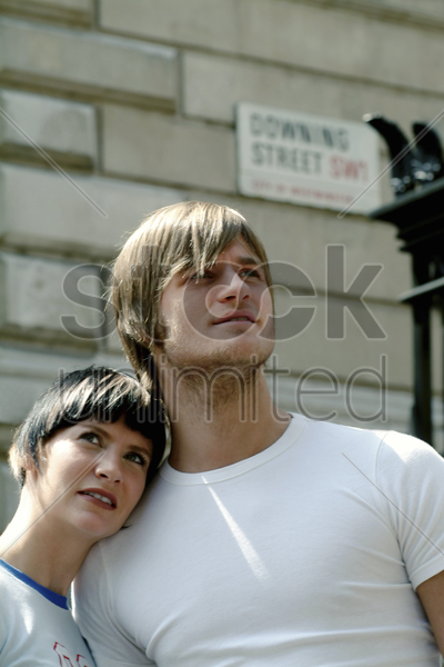 a lady resting her head on her boyfriend's shoulder stock photo