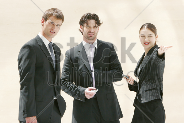 a lady talking to two men in business suits stock photo