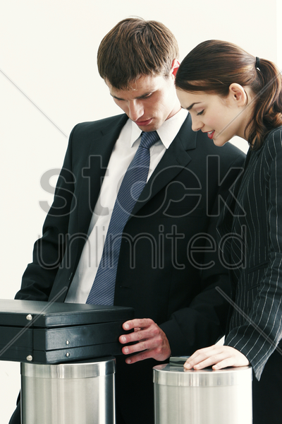 a lady watching as her male colleague opening a briefcase stock photo