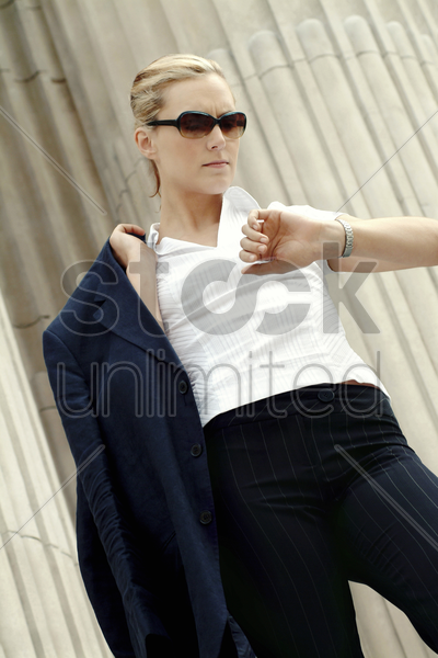 a lady with sunglasses holding a jacket while looking at her watch stock photo