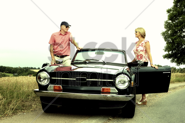 a man and a woman getting into the car stock photo