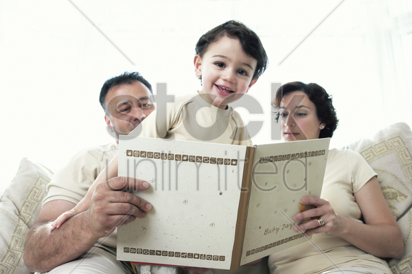 a man and a woman sitting on the couch reading a book for their son stock photo