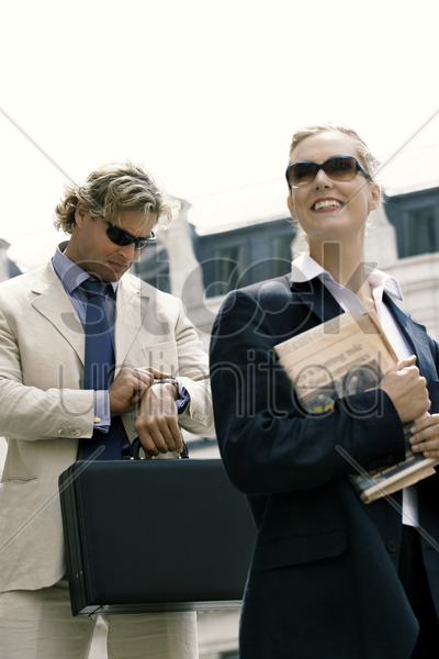 a man and woman in business suit and sunglasses rushing to work stock photo