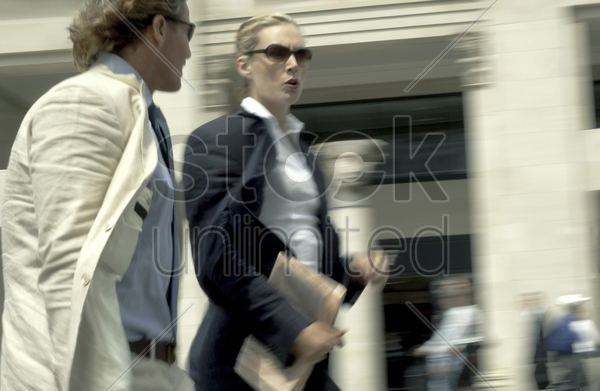 a man and woman in business suit walking in a very fast pace stock photo