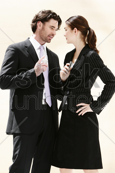 a man and woman standing face to face with each holding a hand phone stock photo