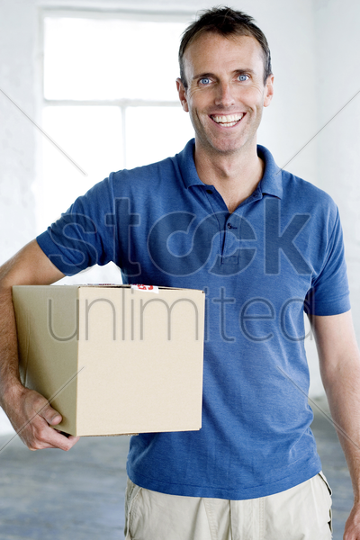 a man carrying a box stock photo