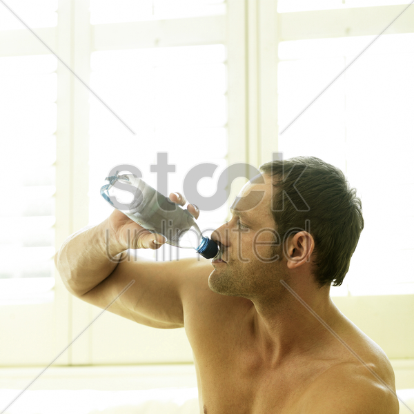 a man drinking water after working out stock photo