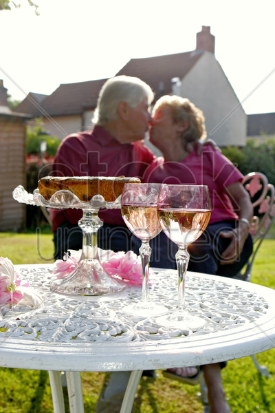 a man giving his wife an anniversary kiss at the garden stock photo