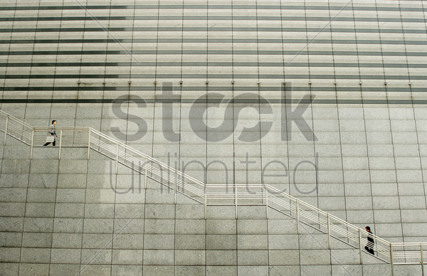 a man going up while another going down the stairs stock photo
