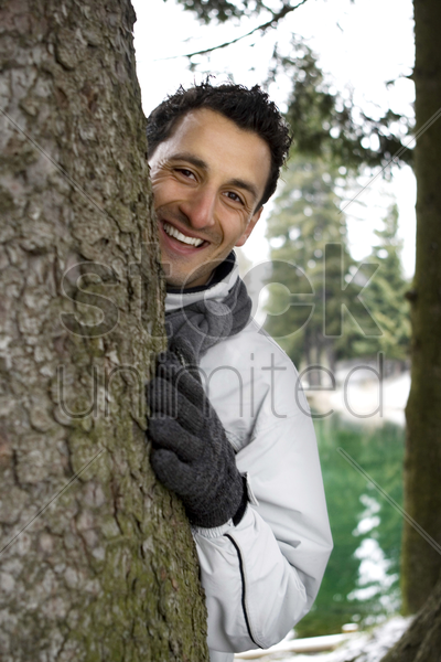 a man hiding behind a tree stock photo