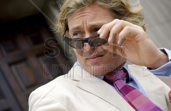 a man in business suit adjusting his sunglass stock photo