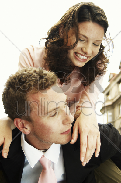 a man in business suit carrying his wife on his back stock photo