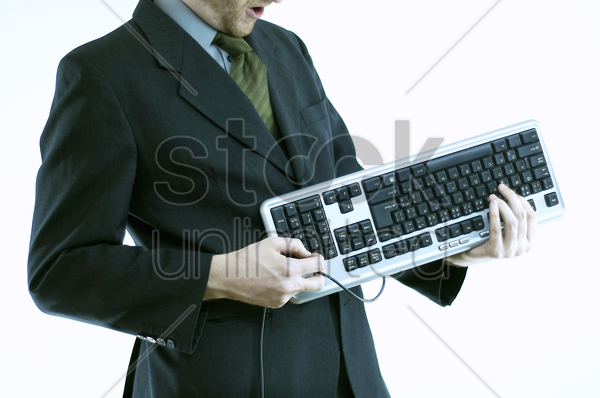 a man in business suit holding a computer keyboard like he is playing a guitar stock photo