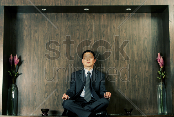 a man in business suit meditating stock photo
