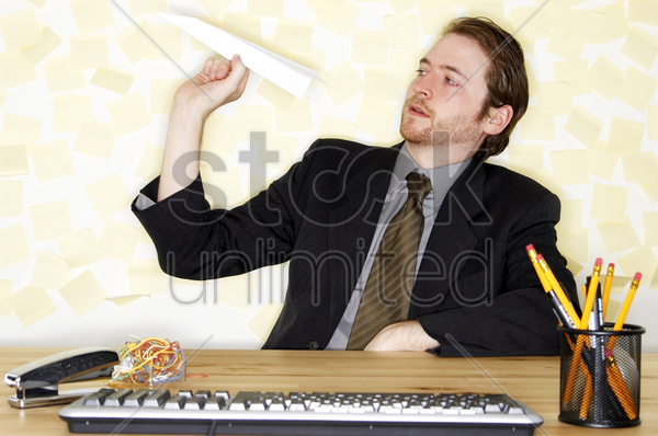 a man in business suit sitting at his desk playing with a paper plane stock photo