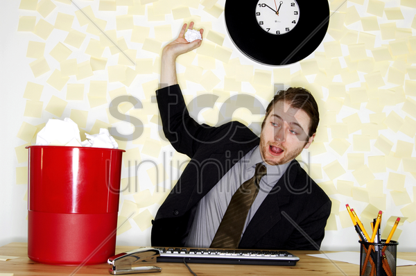 a man in business suit sitting at his desk throwing crumpled paper into the dustbin stock photo