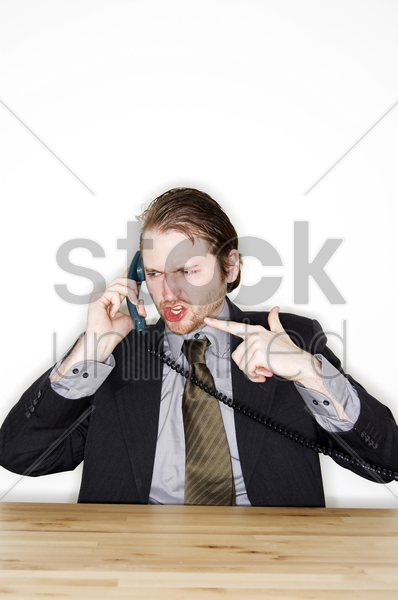 a man in business suit talking angrily on the phone stock photo