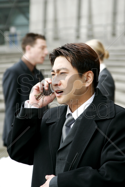 a man in business suit talking on the hand phone stock photo