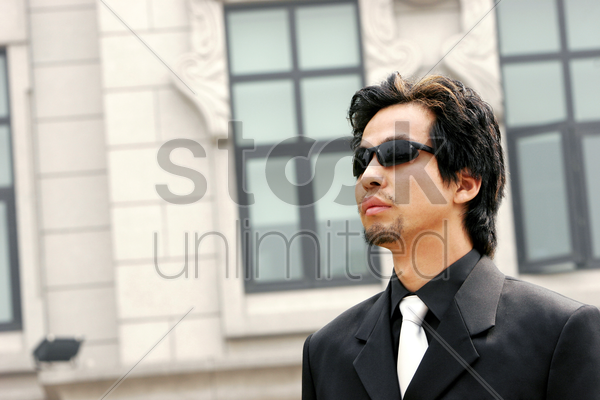 a man in business suit wearing sunglass stock photo