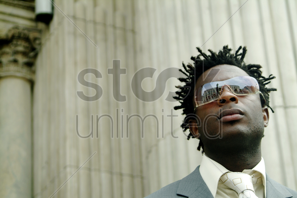 a man in business suit with sunglass looking at the building opposite stock photo