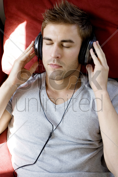 a man listening to music by headphone stock photo