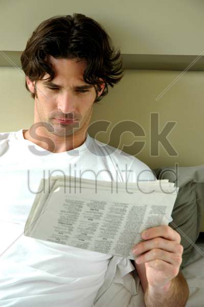 a man lying on his bed reading newspaper stock photo