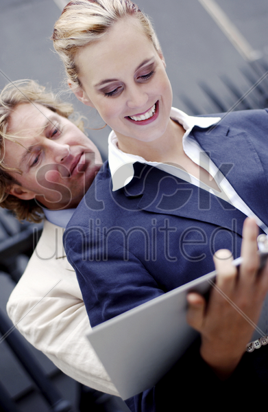 a man resting his chin on his female colleague while reading the notes she is holding stock photo